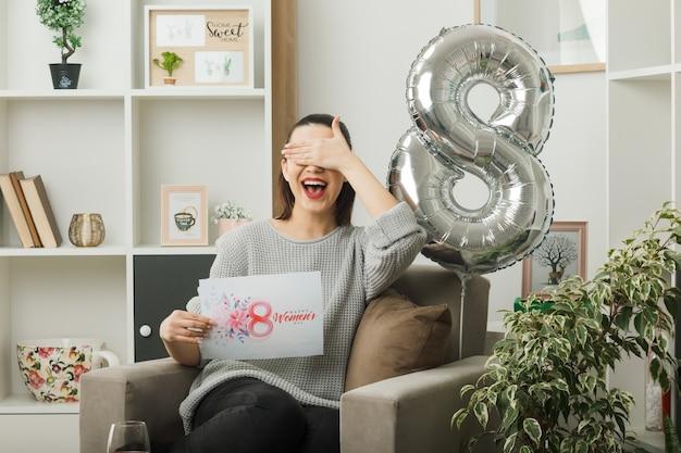 Lächelnde bedeckte augen mit hand schönes mädchen am glücklichen frauentag mit grußkarte auf sessel im wohnzimmer sitzend