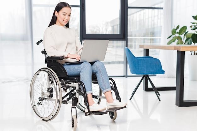 Lächelnde behinderte junge frau, die auf rollstuhl unter verwendung des laptops im büro sitzt