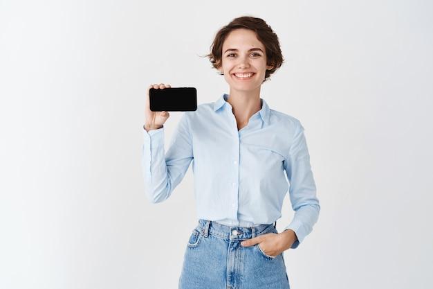 Lächelnde berufsfrau, die den smartphone-bildschirm horizontal hält, die anwendung demonstrieren und auf der weißen wand stehen