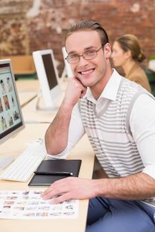 Lächelnde bildeditoren, die computer im büro verwenden
