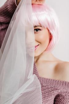 Lächelnde blasse frau mit braunen augen, die gesicht hinter weißem tuch verstecken. innennahaufnahmeporträt des lachenden mädchens im rosa peruke.