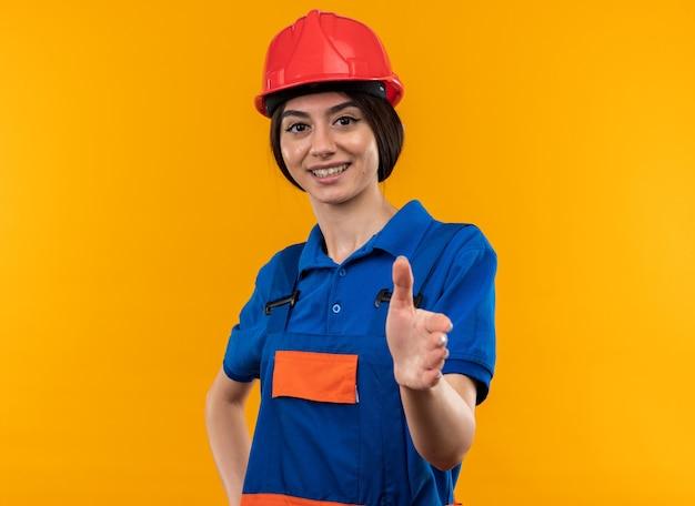 Lächelnde blick in die kamera junge baumeisterin in uniform, die hand in die kamera hält