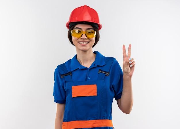 Lächelnde blick in die kamera junge baumeisterin in uniform mit brille, die friedensgeste zeigt