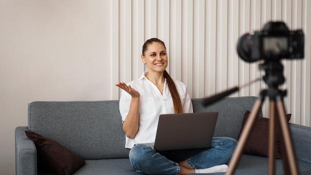 Lächelnde bloggerin nimmt ein neues video auf. sie sitzt zu hause auf der couch und hält einen laptop in der hand. positives business-blog-konzept.