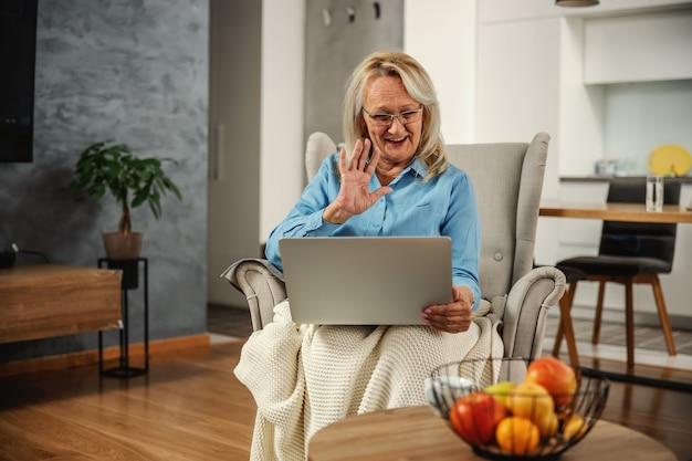 Lächelnde blonde ältere frau, die in einem stuhl sitzt, laptop für online-konversation verwendet und winkt. sie respektiert soziale distanz.