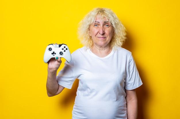 Lächelnde blonde alte frau mit einem joystick in einem weißen t-shirt