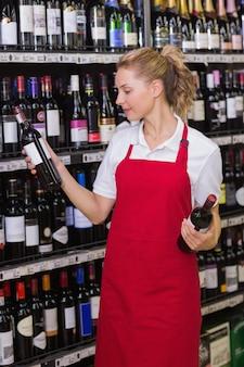 Lächelnde blonde arbeitskraft, die eine weinflasche betrachtet