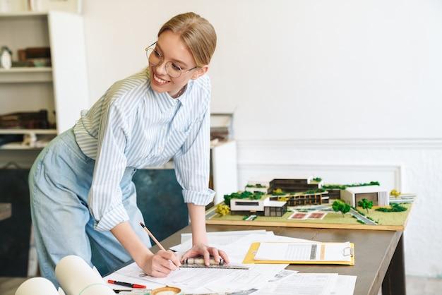 Lächelnde blonde architektin in brillen, die mit zeichnungen arbeitet, während sie entwürfe am arbeitsplatz entwirft