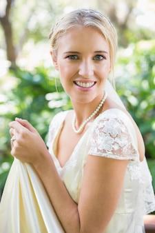 Lächelnde blonde braut, die ihr kleid betrachtet kamera hält