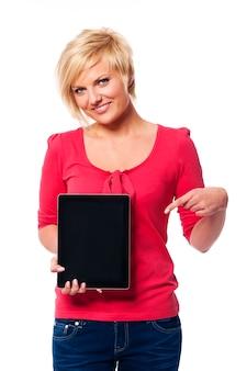 Lächelnde blonde frau, die auf bildschirm des digitalen tabletts zeigt