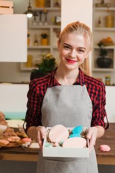 Lächelnde blonde frau, die eine schachtel mit hausgemachten verzierten keksen in der küche hält