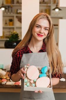 Lächelnde blonde frau, die eine schachtel mit hausgemachten verzierten keksen in der küche hält Premium Fotos