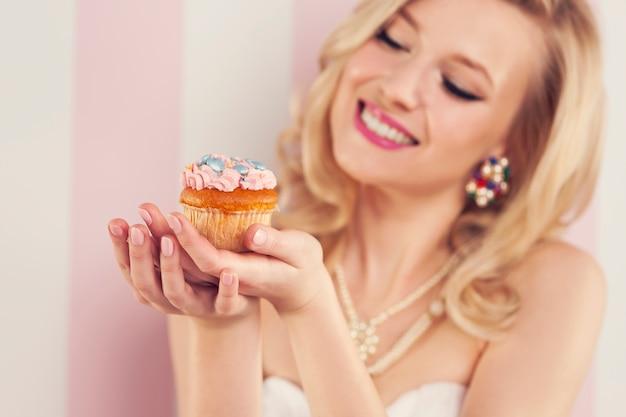 Lächelnde blonde frau, die kleinen muffin hält