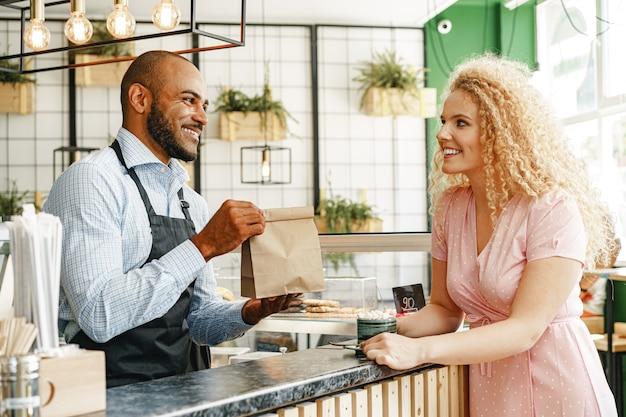 Lächelnde blonde frau, die mit einem kellner eines coffeeshops am thekentisch spricht