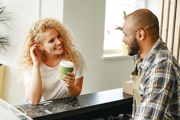 Lächelnde blonde frau, die mit einem kellner eines coffeeshops an der theke spricht