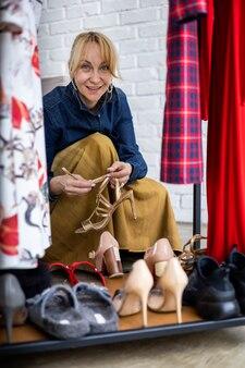 Lächelnde blonde frau, die schuhe im modestudio oder in der boutique auswählt, die das einkaufen genießen?