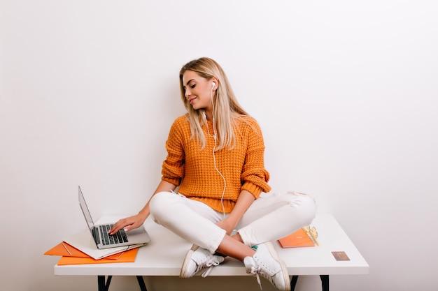 Lächelnde blonde frau, die sich zu hause entspannt, musik hört und etwas auf der tastatur tippt