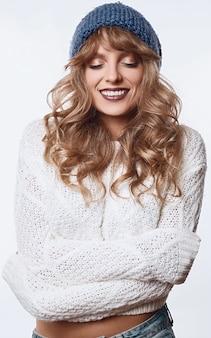 Lächelnde blonde frau in der strickjacke und in hut getrennt auf weiß