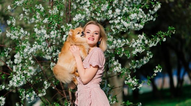 Lächelnde blonde frau mit ihrem pommerschen hund im park