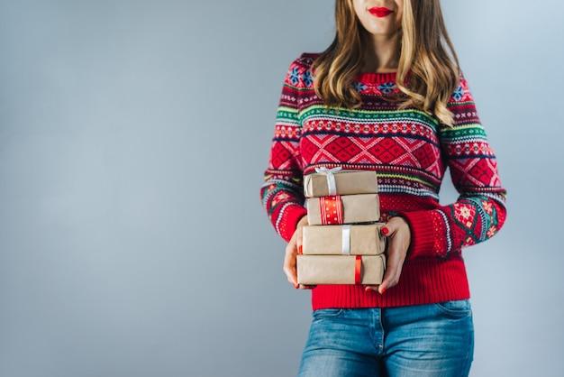 Lächelnde blonde frau mit roten lippen und polierten nägeln, die bündel von geschenkboxen halten, die in bastelpapier eingewickelt und mit rotem satinband verziert werden. weihnachtskonzept