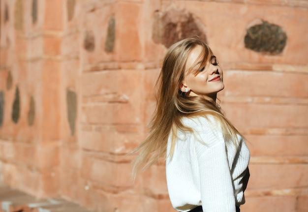 Lächelnde blonde frau mit weißem strickpullover posiert auf der straße mit natürlichem sonnenlicht. platz für text