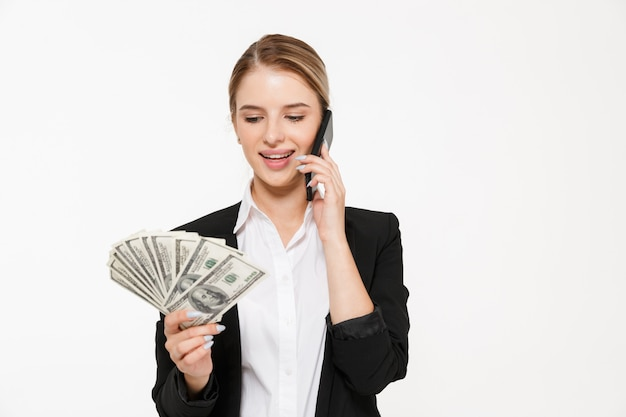 Lächelnde blonde geschäftsfrau, die durch die telefone spricht, während sie geld über weißer wand hält und betrachtet