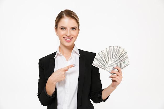 Lächelnde blonde geschäftsfrau, die geld hält und auf ihre während über weiße wand zeigt