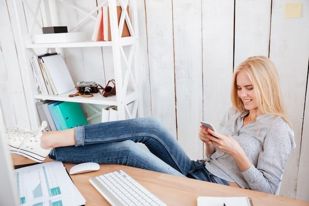 Lächelnde blonde geschäftsfrau, die mit ihren beinen auf dem tisch ruht und handy im büro benutzt