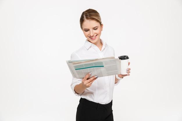 Lächelnde blonde geschäftsfrau, die zeitung liest, während tasse kaffee über weißer wand hält