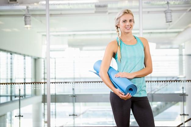 Lächelnde blonde haltene yogamatte in der freizeitmitte