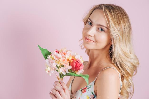 Lächelnde blonde junge frau, die blumenblumenstrauß gegen rosa hintergrund hält