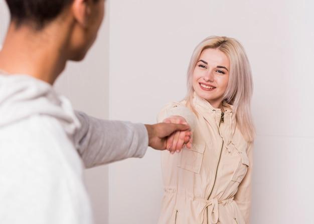 Lächelnde blonde junge frau, die hand ihres freundes hält