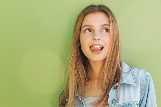 Lächelnde blonde junge frau, die heraus ihre zunge gegen tadellosen grünen hintergrund haftet