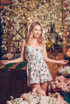 Lächelnde blonde junge frau, die im dekorativen blumengarten steht