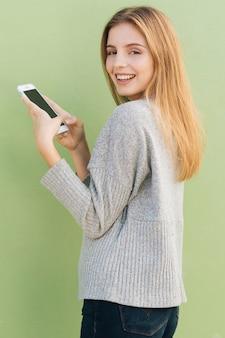 Lächelnde blonde junge frau, die in der hand handy gegen grünen hintergrund hält
