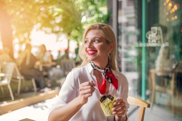 Lächelnde blonde junge frau, die schokoladenmuffin im papierhalter isst
