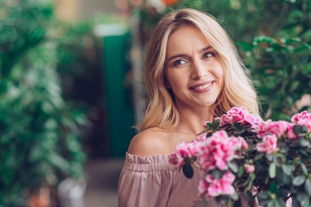 Lächelnde blonde junge frau, die vor blühenden pflanzen steht