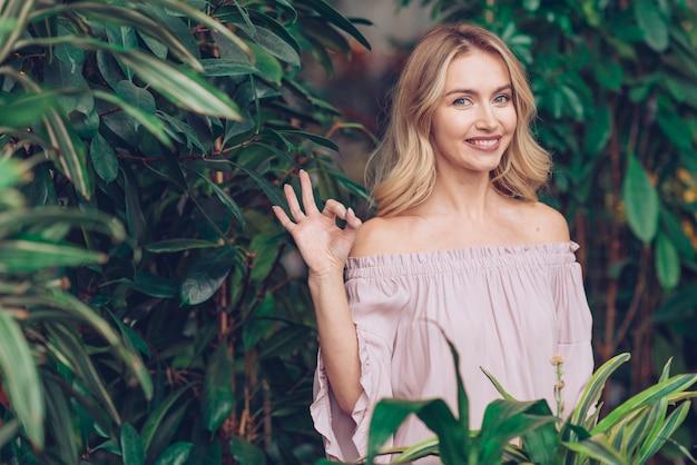 Lächelnde blonde junge frau, die vor der grünpflanze zeigt okayzeichen steht