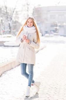 Lächelnde blonde junge frau, die wegwerfkaffeetasse steht auf straße im winter hält