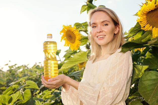 Lächelnde blonde junge frau im weißen kleid, die eine flasche sonnenblumenöl hält, während sie gegen große blumen vor der kamera auf dem feld steht