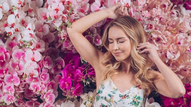 Lächelnde blonde junge frau mit auge schloss stellung gegen bunte orchideen
