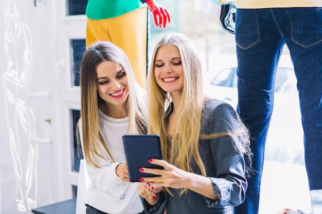 Lächelnde blonde junge frauen, die digitale tablette im shop betrachten