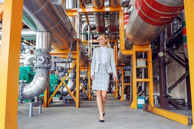 Lächelnde blonde kraftwerksbesitzerin, die herumläuft und maschinen überprüft.