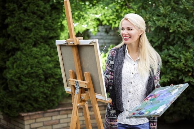 Lächelnde blonde künstlerin mit einem pinsel in der hand zeichnet auf leinwand in der natur.