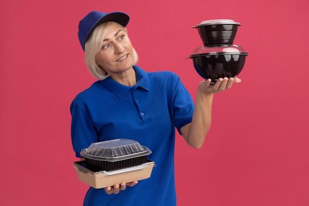 Lächelnde blonde lieferfrau mittleren alters in blauer uniform und mütze, die papiernahrungsmittelpakete und lebensmittelbehälter hält, die lebensmittelbehälter einzeln auf rosafarbener wand betrachten