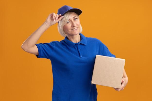 Lächelnde blonde lieferfrau mittleren alters in blauer uniform und mütze mit karton, die ihre mütze greift
