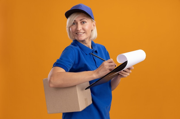 Lächelnde blonde lieferfrau mittleren alters in blauer uniform und mütze