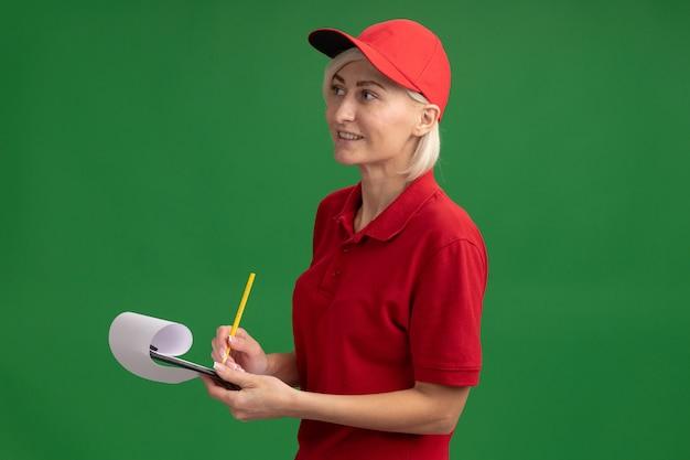Lächelnde blonde lieferfrau mittleren alters in roter uniform und mütze, die in der profilansicht steht und gerade bleistift und zwischenablage hält, isoliert auf grüner wand mit kopierraum