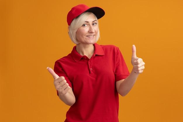 Lächelnde blonde lieferfrau mittleren alters in roter uniform und mütze mit daumen nach oben