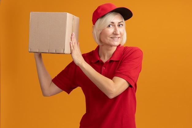 Lächelnde blonde lieferfrau mittleren alters in roter uniform und mütze mit karton in der nähe des kopfes